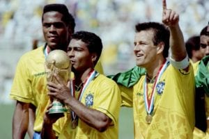 Brazilian forward Romario kisses the FIFA World Cup trophy, flanked by Ronaldao and captain Dunga after Brazil defeated Italy